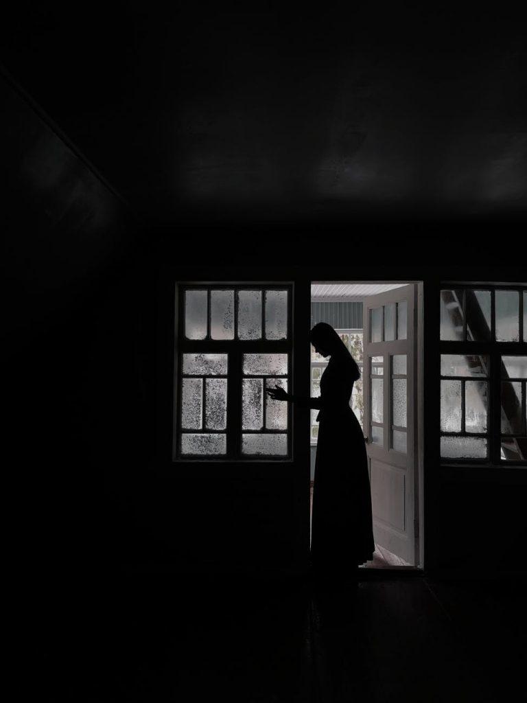 woman in long dress standing in doorway in house